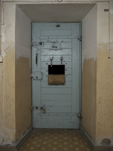 A solitary confinement cell door with open food slot. For many prisoners in solitary receiving their food becomes their most significant human contact.